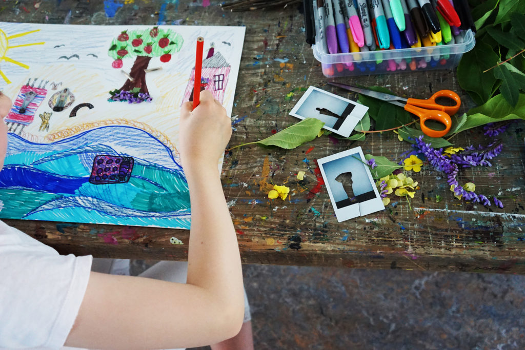 Kulttuurikeskus ARXin kesän työpajatoimintaa. Kuvassa on kyniä, sakset, leikattuja valokuvia ja piirustuspaperia. Lapsi piirtää kesäistä maisemaa.