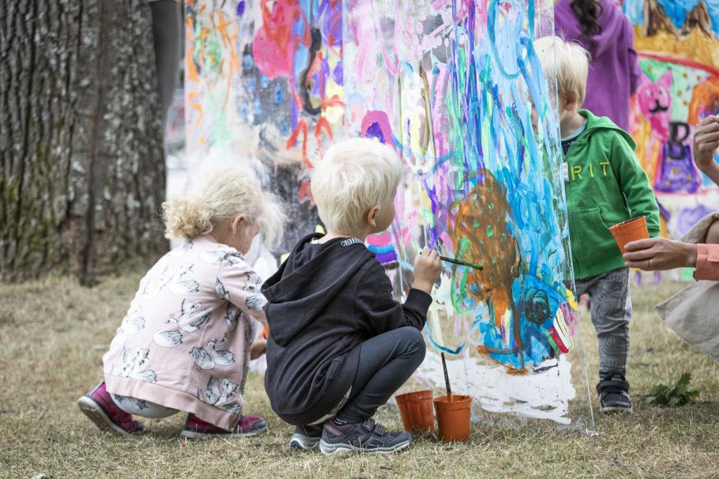 Lapset maalaamassa ulkona.