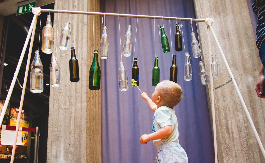Kuvassa on vedellä täytettyjä lasipulloja roikkumassa naruilla ilmassa ja lapsi kurkottaa soittamaan pulloa kepillä.
