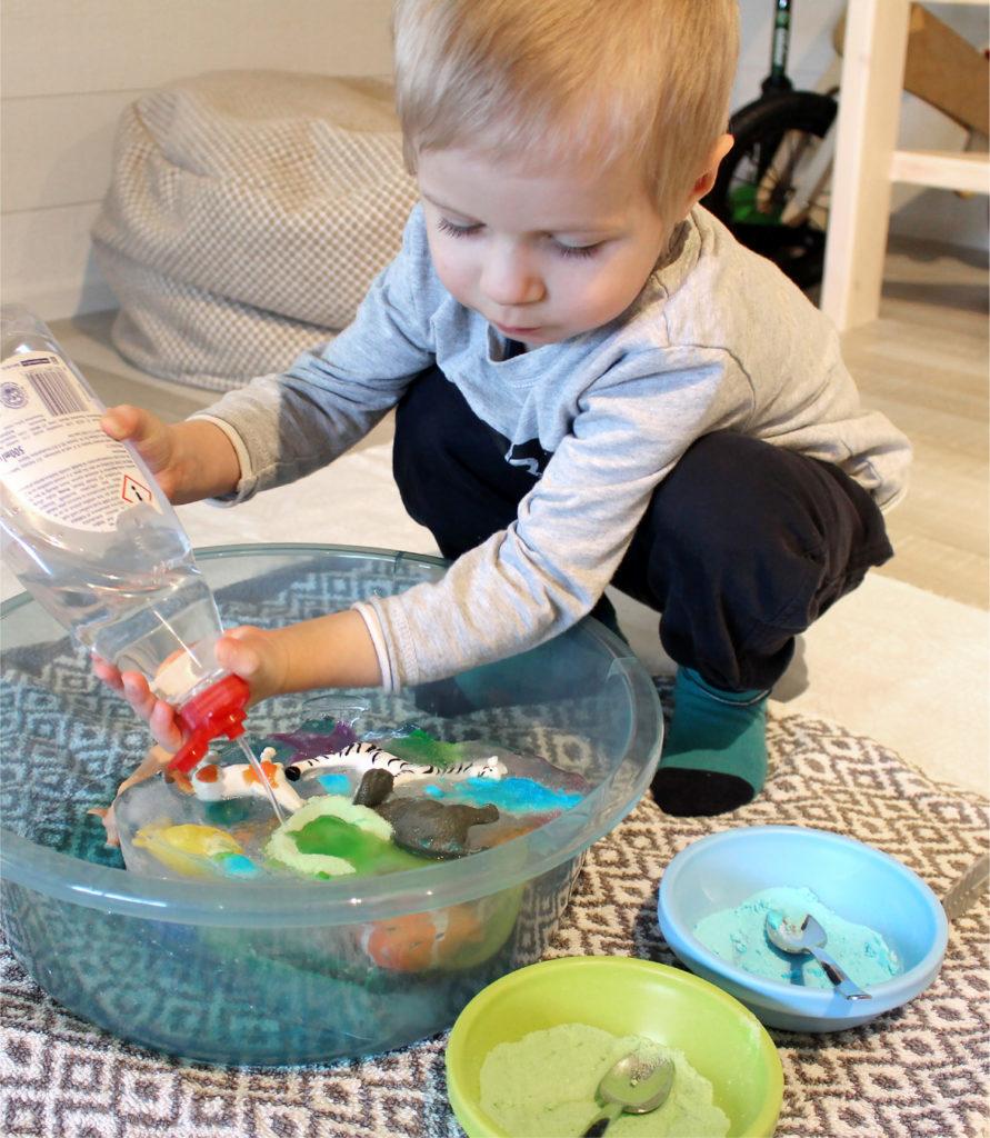 Kuvassa lapsi pelastamassa muovieläimiä jääpalan sisältä.