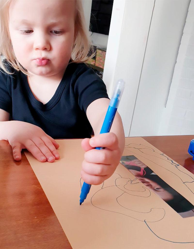Kuvassa lapsi piirtää tussilla paperiin.