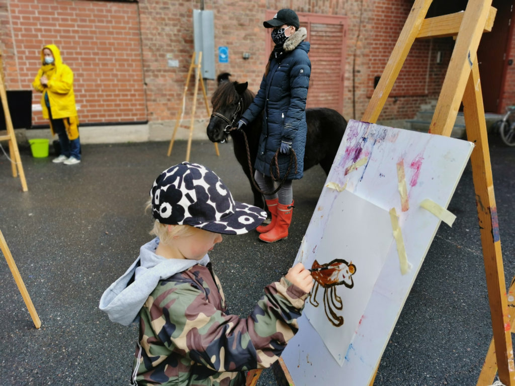 Syysloman Kujahulinat 2020. Kuvassa lapsi maalaa mallina olevaa ponia ulkona Verkatehtaan pihalla.