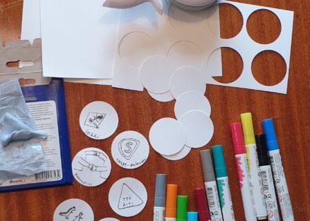 Kuvassa etätyöpäivän kalenterin askarteluun tarvittavia välineitä. Mm. paperia, kyniä, leikkuri ja sinitarraa.