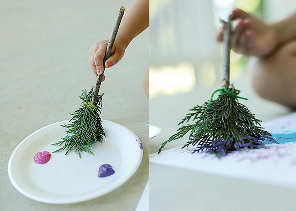 Kuvassa maalataan luonnosta kerätyillä ja itsetehdyillä pensseleillä.
