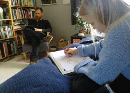 Kuvassa lapsi piirtämässä aikuisen muotokuvaa paperille.