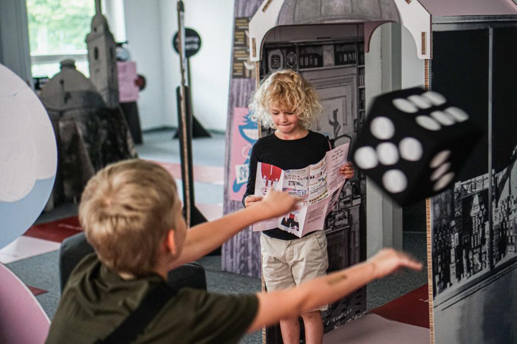 Kuvassa lapset pelaamassa Skidipeliä Galleria ARXissa. Kuvassa toinen lapsi heittää isoa pelinoppaa.