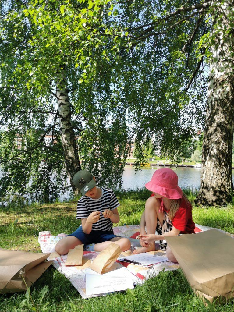 Kaksi lasta puistossa taiteilemassa