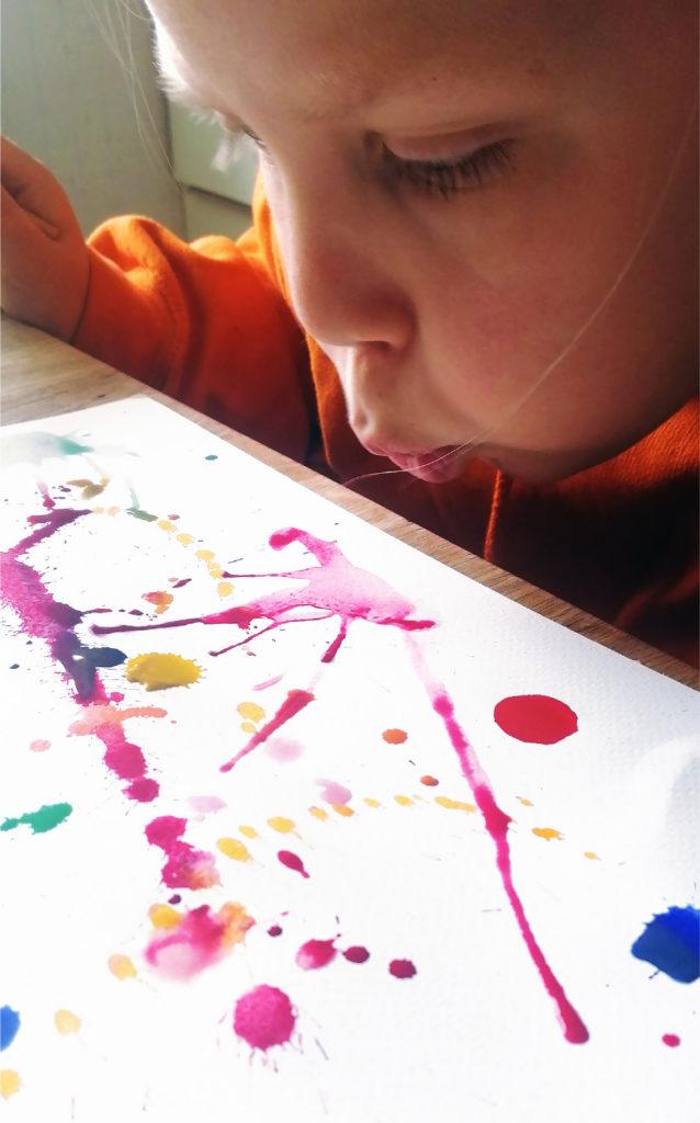 Kuvassa lapsi puhaltaa paperille tiputettuja väripisaroita rikki.